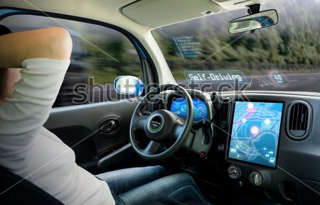Image of a man in a car with hands off the wheel